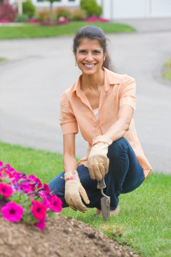 Woman working in her flower garden : Stock Photo
