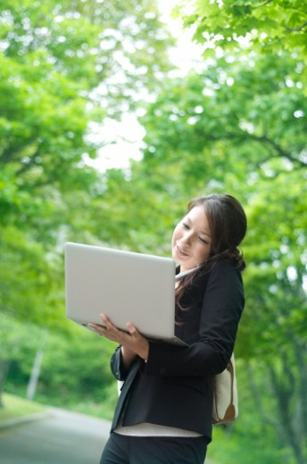 Business woman using a laptop and mobile phone : Stock Photo