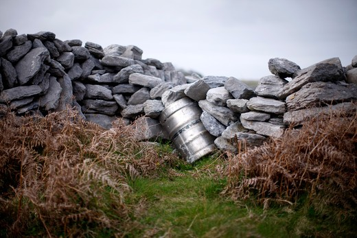 A keg holds up a traditional Irish stone wall on the Aran Islands in place of missing limestone slab.  : Stock Photo