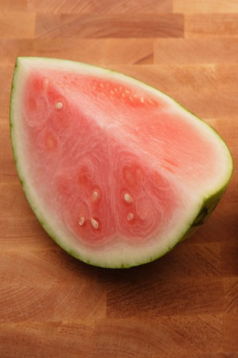 A slice of seedless watermelon on a wood chopping block. : Stock Photo