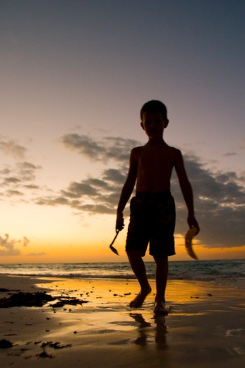 Stock Photo: 1598R-10016620 Mexico, Yucatan, Isla Mujeres (Island of Women), boy (age 8) building sand castle on beach at sunset  MR