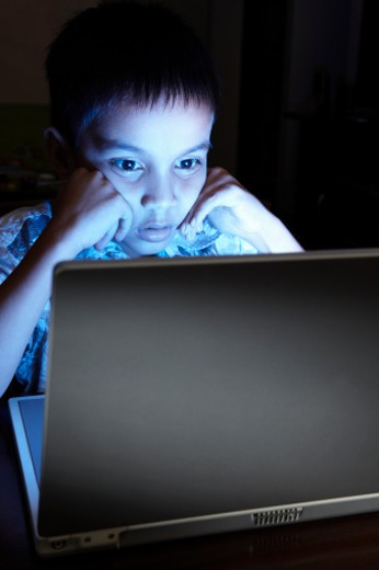 Adolescent boy using laptop at night. : Stock Photo