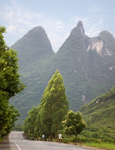 Stock Photo: 1598R-10018213 Bicyclists on a road leading to Yangshuo, with the famous karsts (pointed hills) of Guangxi Province in the background