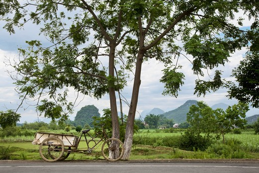 A bicycle cart on a road near Yangshuo with the famous karsts (pointed hills) in the background. : Stock Photo