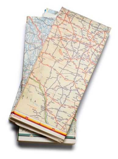 Stock Photo: 1598R-10019880 A stack of folded road maps on a white background.