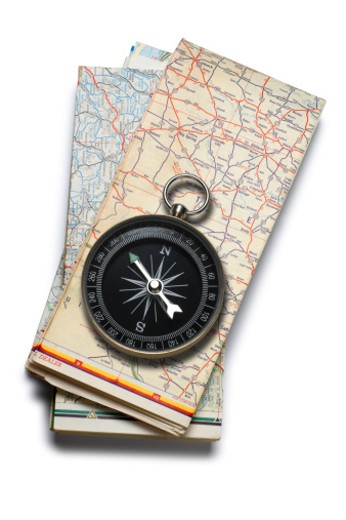 Stock Photo: 1598R-10019881 A compass sitting on a stack of folded road maps on a white background.