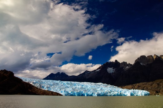 Stock Photo: 1598R-10020120 The Cordillera del Paine is a small but spectacular mountain group in Torres del Paine National Park in Chilean Patagonia. From time to time the glacier drops giant pieces of ice that are carried to the shore by the wind.