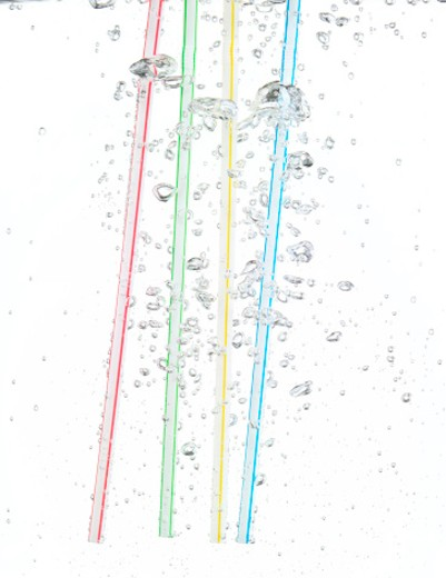 Four straws underwater and blowing bubbles on a white background in studio : Stock Photo