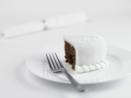 Stock Photo: 1598R-10020553 Slice of wedding cake with napkin in background