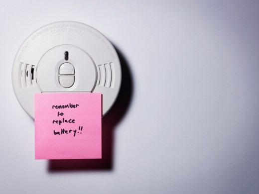 Stock Photo: 1598R-10020838 Plastic smoke detector with 'remember to replace the battery' note.