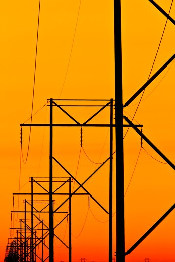 Electirc power lines and with orange sky at dawn, Frazer, Montana, USA : Stock Photo