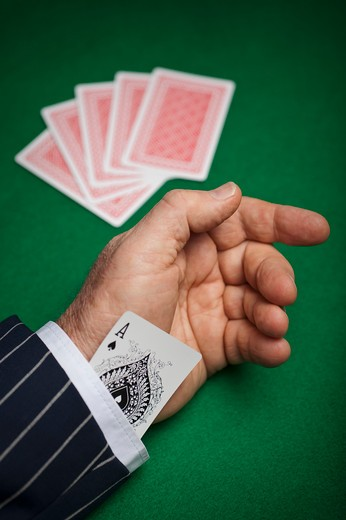 A playing card tucked in the sleeve of a mans suit : Stock Photo