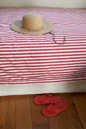 Stock Photo: 1598R-10021417 Sun hat  on a bed and sandals