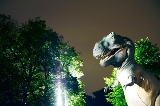 Dinosaur and trees at night : Stock Photo