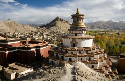 The Kumbum Stupa at Pelkor Chode Monastery in Gyantse in Tibet. Gyantse Dzong is on the hilltop in the background. : Stock Photo