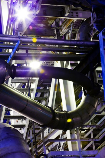 Detail of pipes, catwalks, and conduit at night in an aluminum processing factory : Stock Photo