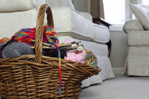 Basket on living floor filled with knitting supplies : Stock Photo