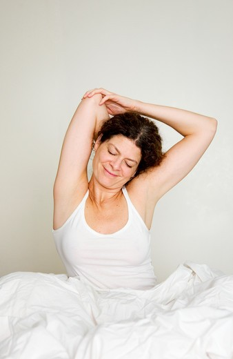 Stock Photo: 1598R-10023898 Woman stretching in bed