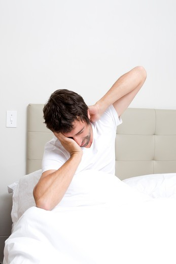 Stock Photo: 1598R-10023997 Man stretching in bed