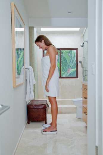 Woman in towel weighing self in bathroom : Stock Photo