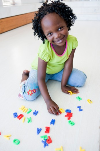 Girl playing with letters of the alphabet : Stock Photo