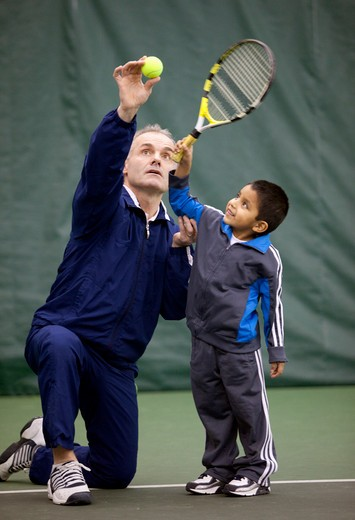 Tennis teacher holds a ball for a five year old learning how to serve.   : Stock Photo
