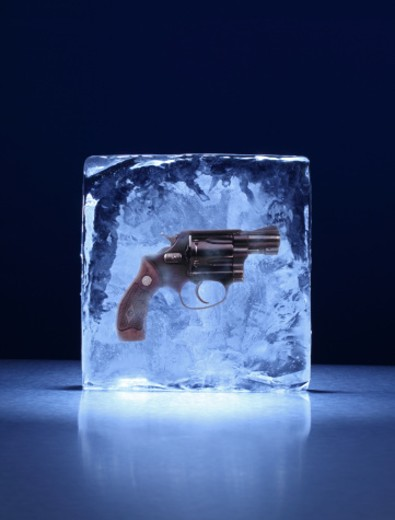 A square shaped block of ice with a hand gun frozen inside : Stock Photo
