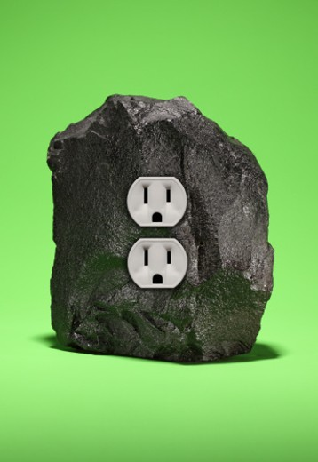 A large piece of black coal with two electrical outlets on a bright green surface : Stock Photo