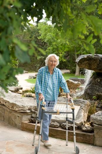 Stock Photo: 1598R-10030391 Elderly woman with a walker walking outside.