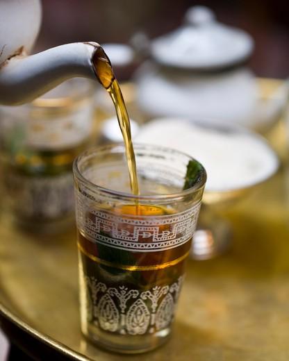 Mint tea poured into traditional tea glass : Stock Photo