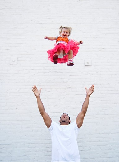 Father tossing baby girl into air : Stock Photo