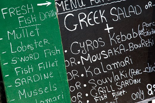 Stock Photo: 1598R-10031045 Greek menu written with chalk on a board. The board has two colours, green and black and the menu is written with white chalk. It consists of Greek dishes mainly fish. The frame of the photograph is horizontal.