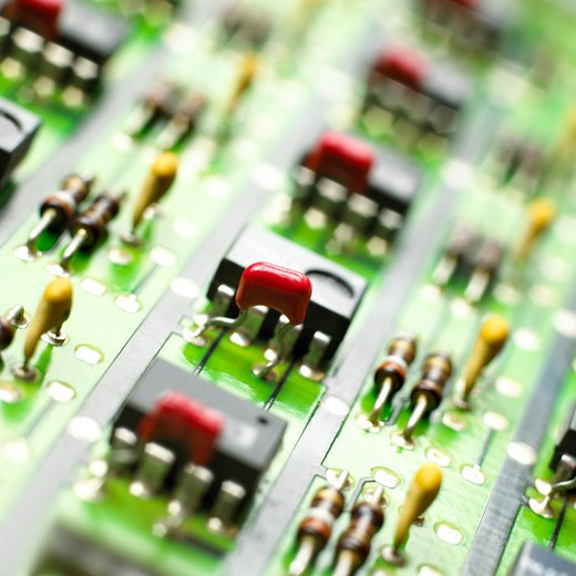 Circuit board photographed close up. The photograph is square and full frame. Only parts of the board can be seen. The circuit can be seen in perspective and it has been taken indoors. : Stock Photo