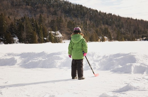 Stock Photo: 1598R-10031087 Little girl and hockey stick on frozen lake