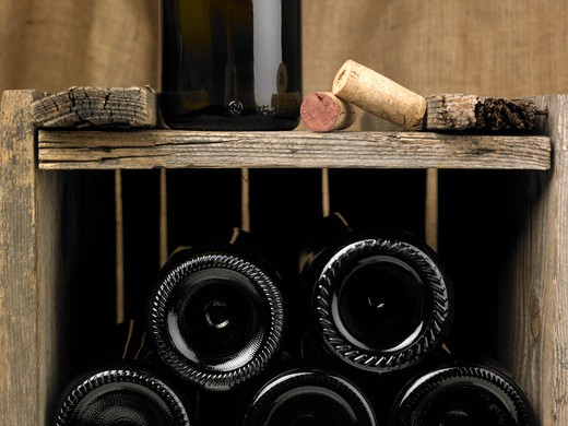 Wine bottles in a wine cellar. Only the bottom of the bottles can be seen as well as some details of the cellar, such as some corcks and part of a bottle.The frame of the photograph is horizontal. : Stock Photo