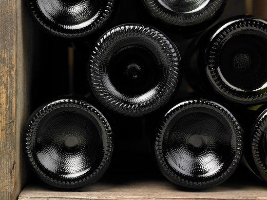 Wine bottles in a wine cellar. Only the bottom of the bottles can be seen close up. The frame of the photograph is horizontal. : Stock Photo