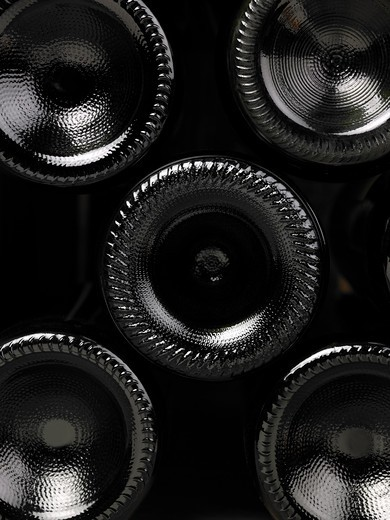 Stock Photo: 1598R-10032852 Wine bottles in a wine cellar. Only the bottom of the bottles can be seen close up. The frame of the photograph is vertical.