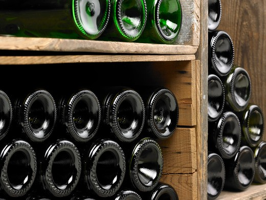 Wine bottles in a wine cellar. Only the bottom of the bottles can be seen as well as some details of the cellar. The frame of the photograph is horizontal and the bottles have been shot in perspective. : Stock Photo
