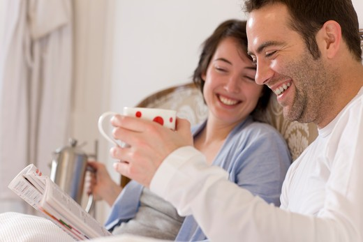 Couple [M+F] in bed having breakfast reading magazine smiling. : Stock Photo