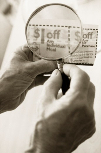 Reading Coupons with Magnifier : Stock Photo