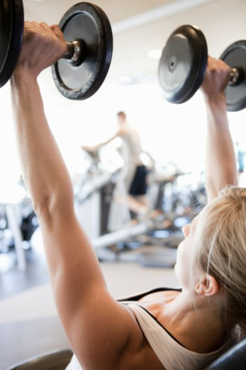 Stock Photo: 1598R-10038715 young woman doing bench press with dumbbells in a weight gym