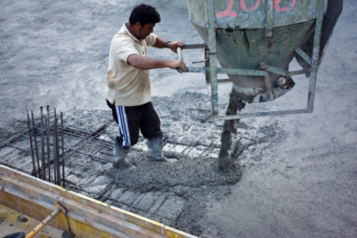 Builder pouring concrete from a hopper : Stock Photo