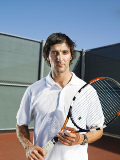 Man holding tennis racket, portrait : Stock Photo