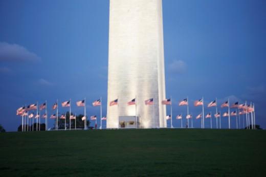 USA, Washington DC, Washington Monument with US flags at dawn : Stock Photo