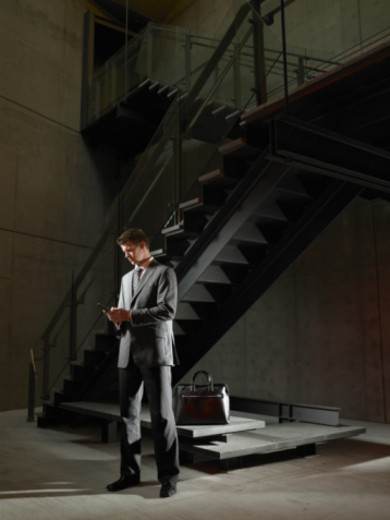 Young businessman standing beside stairway, using cell phone : Stock Photo