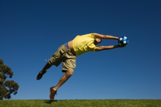 Man leaping to catch soccer ball : Stock Photo
