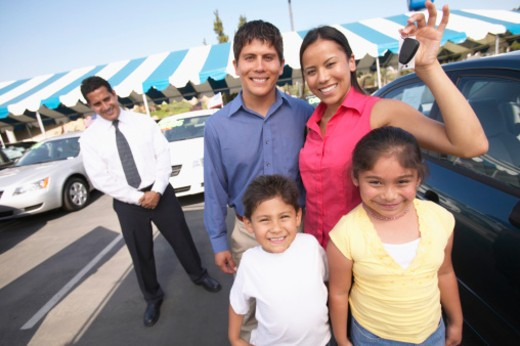 Family in car lot, mother holding keys, smiling, portrait : Stock Photo