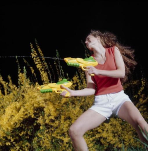 Woman Firing Squirt Guns : Stock Photo