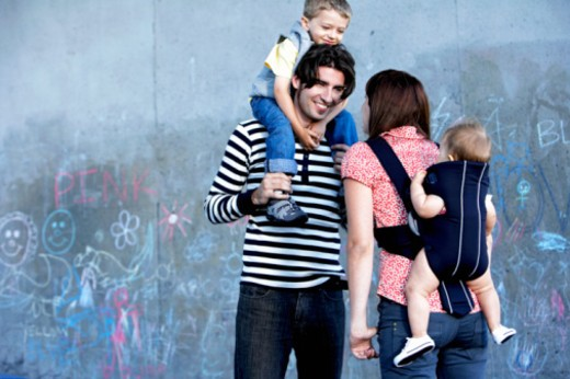Man carrying son (2-4) and woman carrying baby (6-9 months), outdoors : Stock Photo