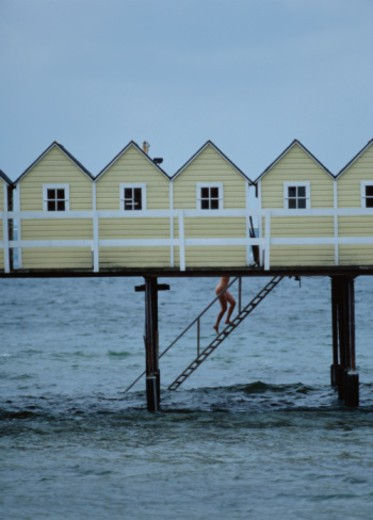 Stock Photo: 1598R-10046570 Nude Woman and Huts on Pier